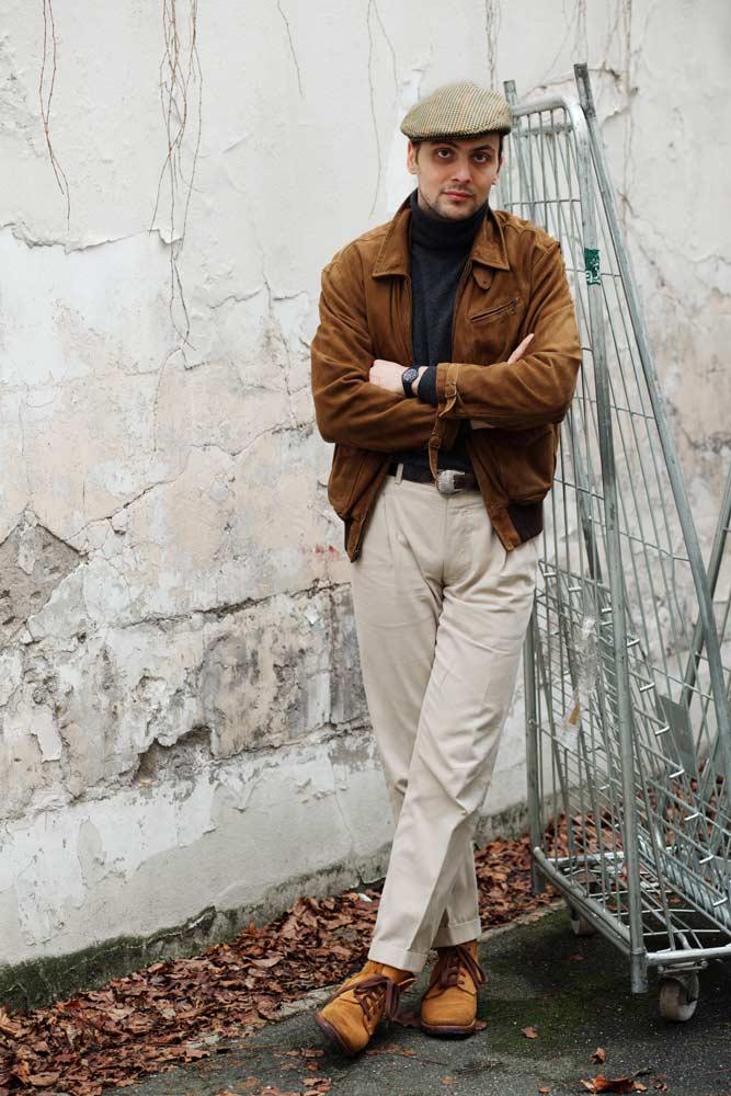 Stéphane Butticé avec un blouson en daim marron, pantalon blanc et casquette en tweed.