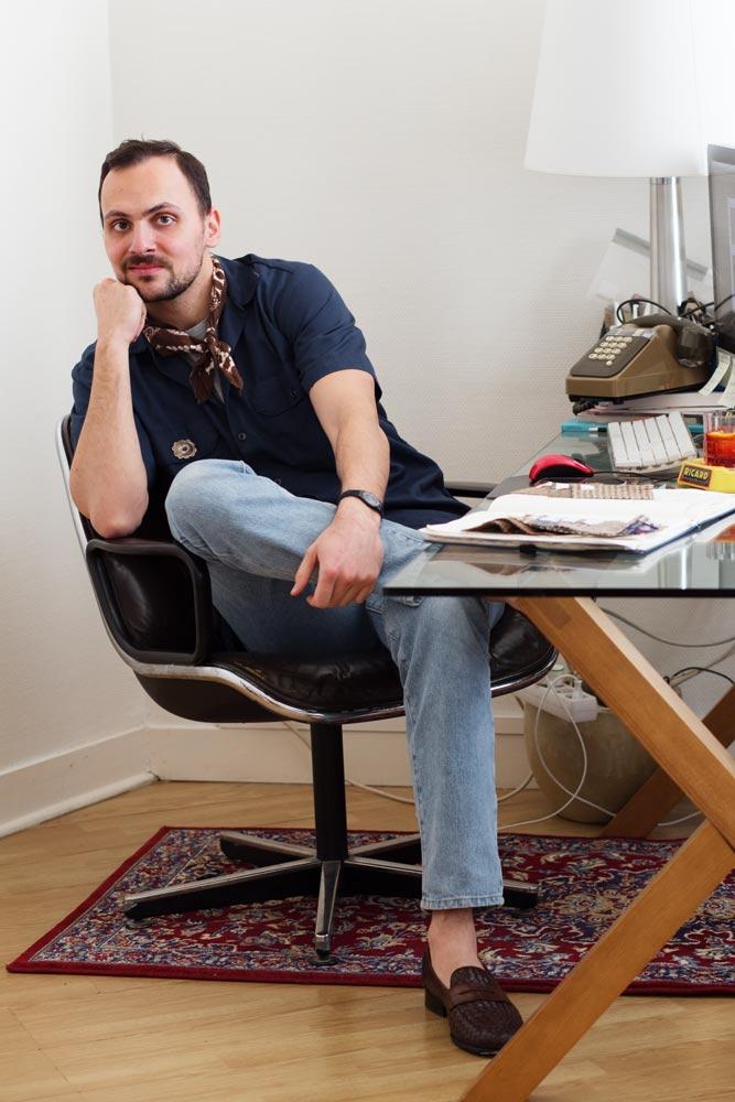 Stéphane Butticé sur son fauteuil Charles Pollock Knoll avec un jean et une chemise à manches courtes bleue.