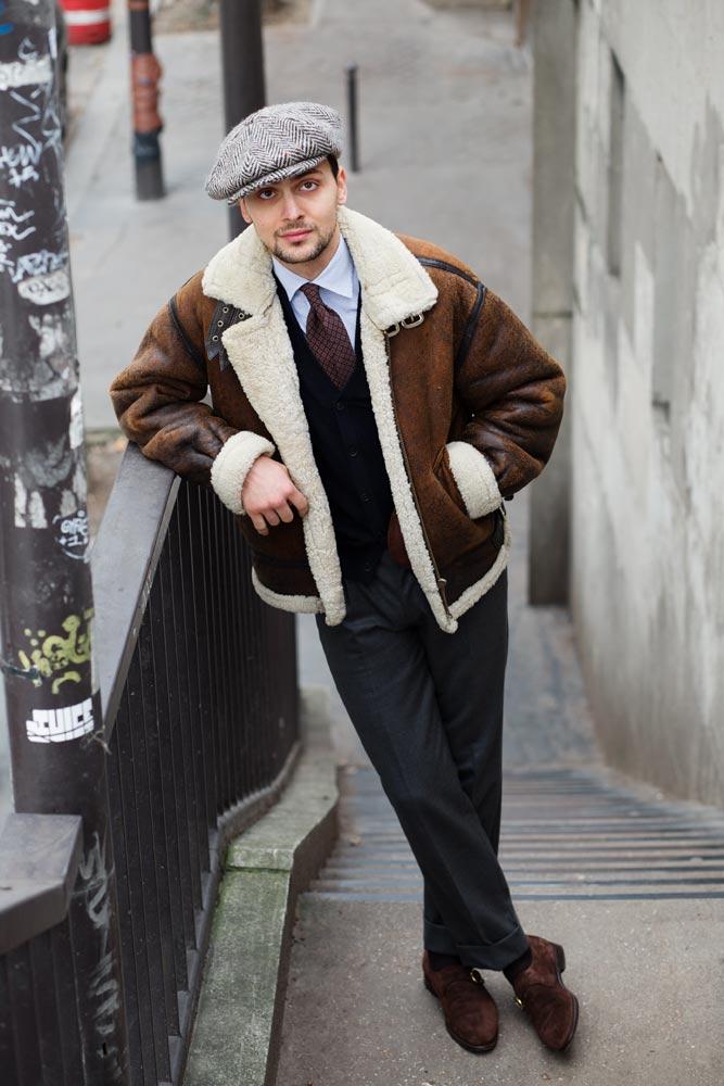 Stéphane Butticé avec un blouson en peau lainée, chemise sartoriale Avino Laboratorio Napoletano ainsi qu'un pantalon gris, casquette en tweed et chaussures mono boucle Barbanera.