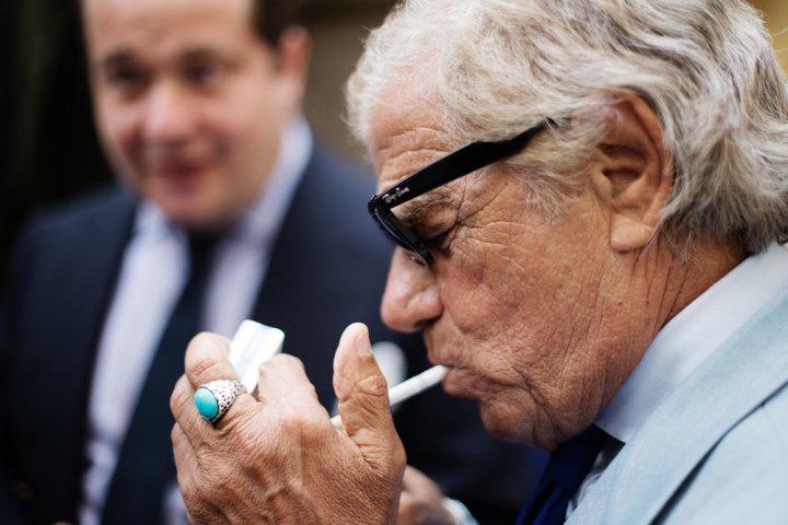 Lino Ieluzzi de la boutique de prêt à porter masculin Al Bazar en train de s'allumer une cigarette.