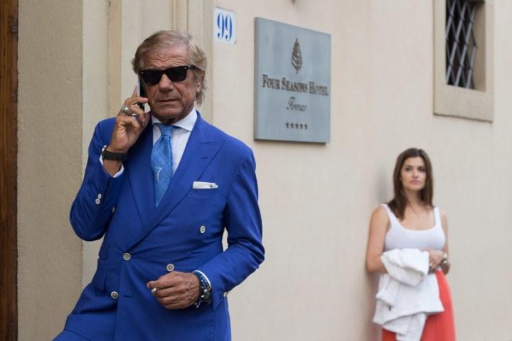 Lino Ieluzzi de la boutique de vêtements pour homme Al Bazar au téléphone à l'entrée d'un palace à Florence.