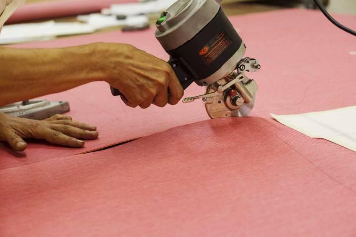 Découpage d'un tissu de chemise chez Avino Laboratorio Napoletano.