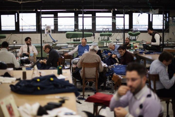 Tailleurs et couturiers assis sur des chaises de bistrot dans l'atelier de productions de costumes faits main Kiton. La Maison de couture de tailleurs Napolitaine Kiton. Kiton a industrialisé le processus de création de costumes de tailleurs réalisés à la main.