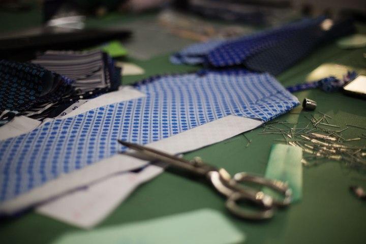 Du tissu de soie à cravate et une paire de ciseaux dans une table de coupe Kiton. La Maison de couture de tailleurs Napolitaine Kiton a Arzano. Kiton a industrialisé le processus de création de costumes de tailleurs réalisés à la main.