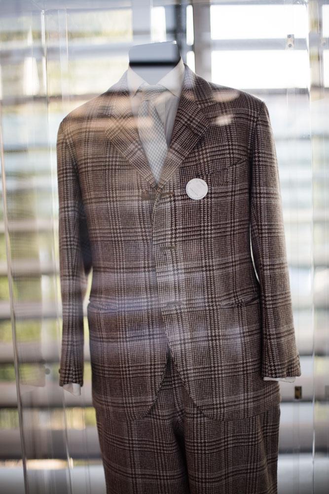 Costume à motif prince de galles sur mesure ayant appartenu au Duc de Windsor dans une vitrine de la passerelle servant à relier deux sites de production du complexe Kiton. La Maison de couture de tailleurs Napolitaine Kiton a Arzano. Kiton a industrialisé le processus de création de costumes de tailleurs réalisés à la main.