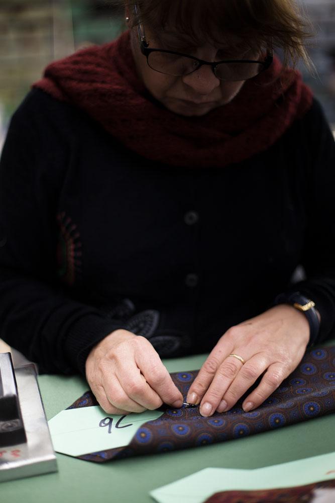 Couturière qui épingle une cravate en soie Kiton. La Maison de couture de tailleurs Napolitaine Kiton a Arzano. Kiton a industrialisé le processus de création de costumes de tailleurs réalisés à la main.