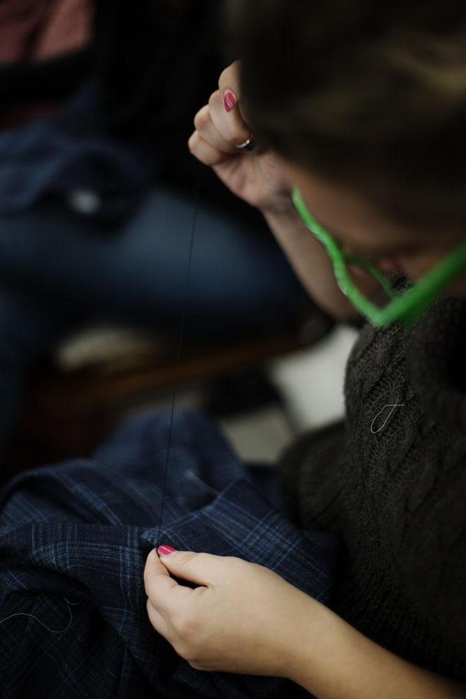 Couturière avec lunettes vertes dans l'atelier de production de vestes faites à la main Kiton. La Maison de couture de tailleurs Napolitaine Kiton. Kiton a industrialisé le processus de création de costumes de tailleurs réalisés à la main.