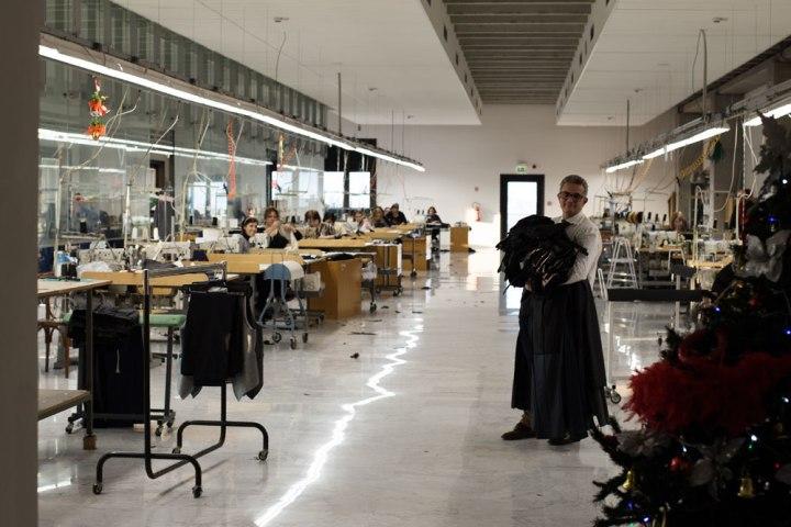 Culottier avec pantalons dans les bras dans la pièce de l'atelier Kiton servant à réaliser des pantalons. La Maison de couture de tailleurs Napolitaine Kiton a Arzano. Kiton a industrialisé le processus de création de costumes de tailleurs réalisés à la main.