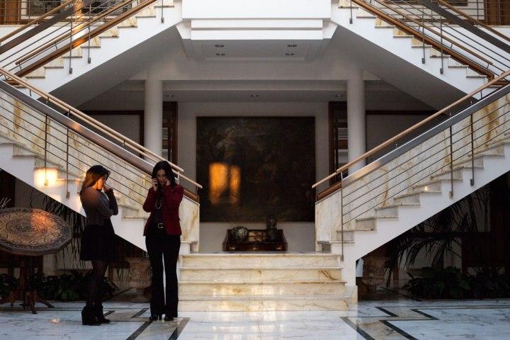 Hall d'entrée de la Maison de couture de tailleurs Napolitaine Kiton remplie d'oeuvres d'art et de deux femmes. Kiton a industrialisé le processus de création de costumes de tailleurs réalisés à la main.