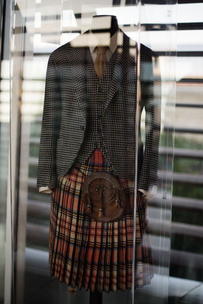 Veste à motif pied de poule et kilt black watch sur mesure ayant appartenu au Duc de Windsor dans une vitrine de la passerelle servant à relier deux sites de production du complexe Kiton. La Maison de couture de tailleurs Napolitaine Kiton a Arzano. Kiton a industrialisé le processus de création de costumes de tailleurs réalisés à la main.