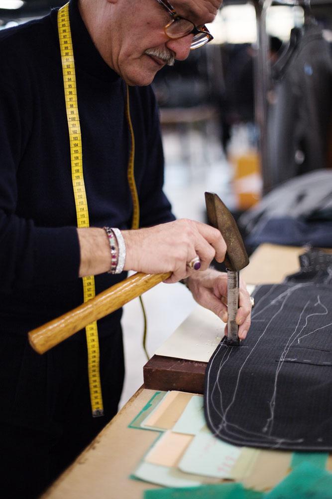 Un tailleur est entrain de donner un coup de marteau pour créer la boutonnière sur la veste Kiton réalisée à la main. La Maison de couture de tailleurs Napolitaine Kiton. Kiton a industrialisé le processus de création de costumes de tailleurs réalisés à la main.