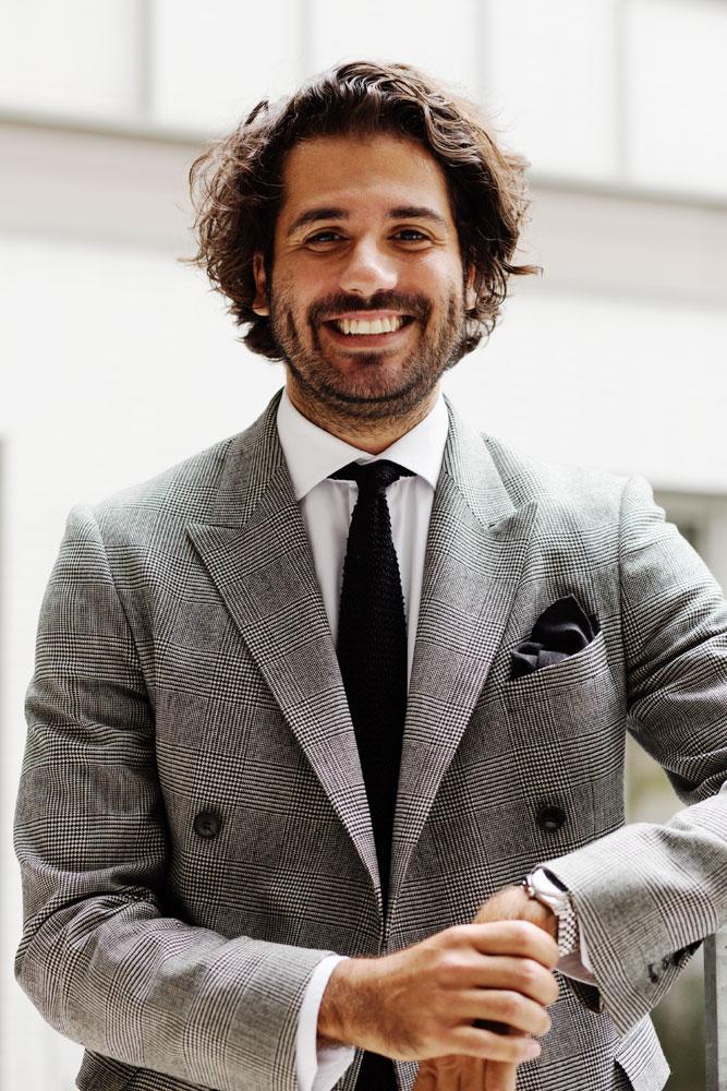 Alexandre Dray en costume prince de galles noir et blanc croisé et cravate tricot noire souriant dans le campus Publicis et Nous avant de travailler pour la campagne pub Kiton.