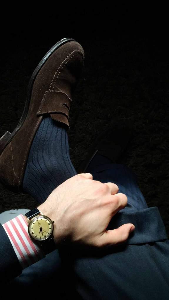Montre Omega seamaster vintage sur costume bleu en laine et chemise rayée frmboise.